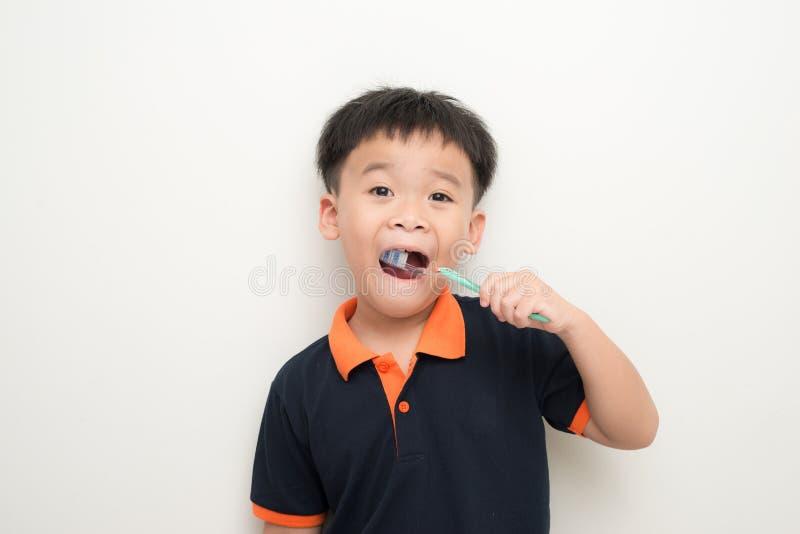 Chłopiec szczotkuje jego zęby na białym tle zdjęcia stock