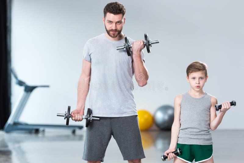 Chłopiec szkolenie z dumbbells wraz z trenerem zdjęcia stock