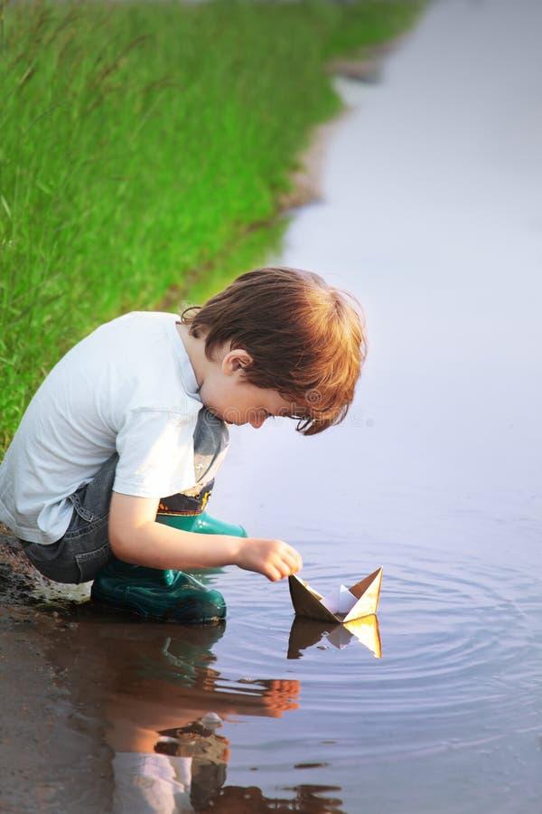 Chłopiec sztuka w papierowym statku w kałuży zdjęcia stock