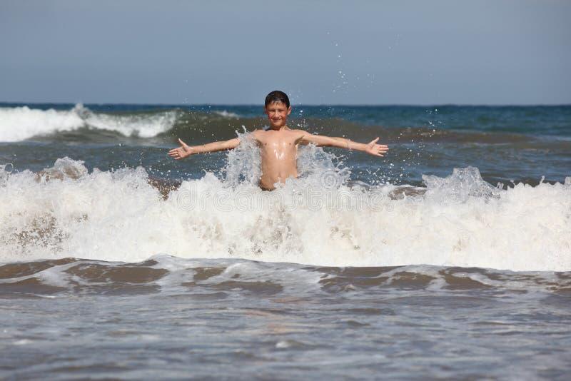Chłopiec sztuka z ocean fala fotografia stock