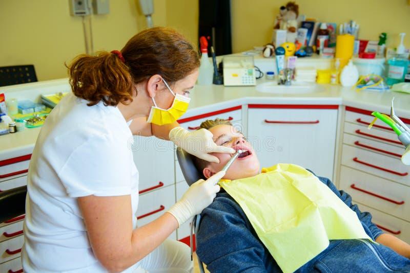 Chłopiec taktuje żeńskim dentystą obraz royalty free