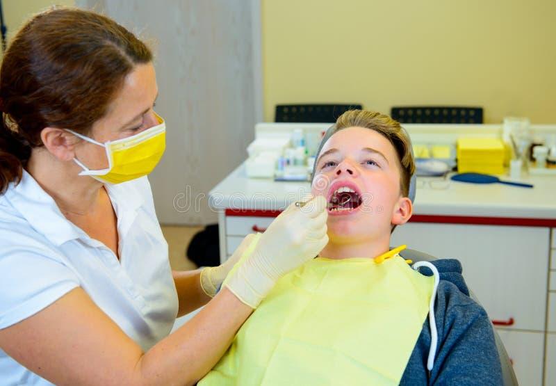 Chłopiec taktuje żeńskim dentystą obrazy stock