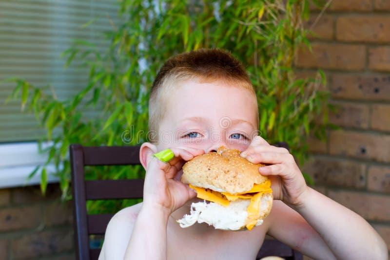 Chłopiec target986_1_ ogromnego hamburger zdjęcie stock