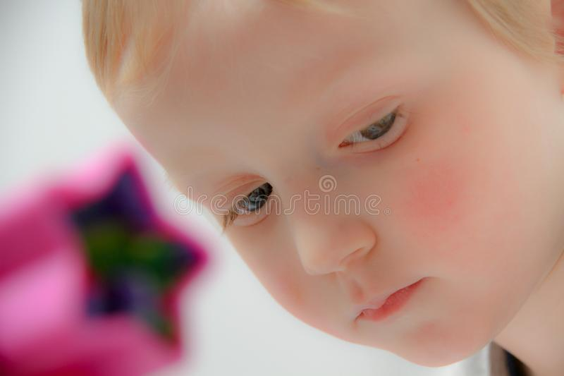 Chłopiec trzy lat siedzi na sztuki z i stole plasteliną, zabawki, sześciany i kostka do gry drewnianymi i plastikowymi, zdjęcie royalty free