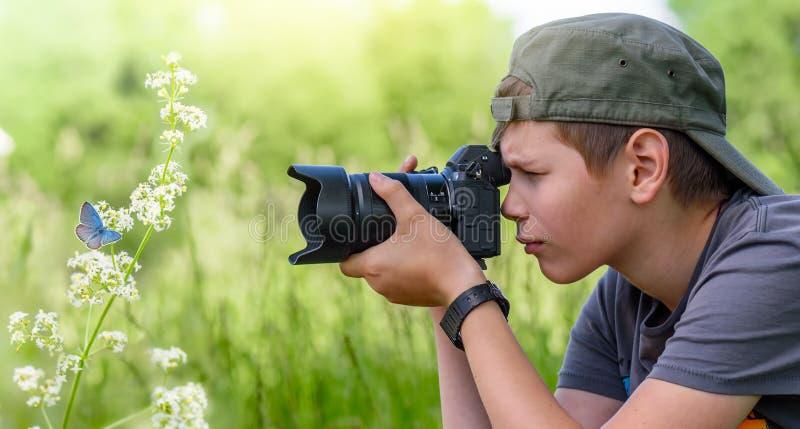 Chłopiec trzyma cyfrowej kamery i strzelaniny motyla na dzikim kwiacie obrazy royalty free