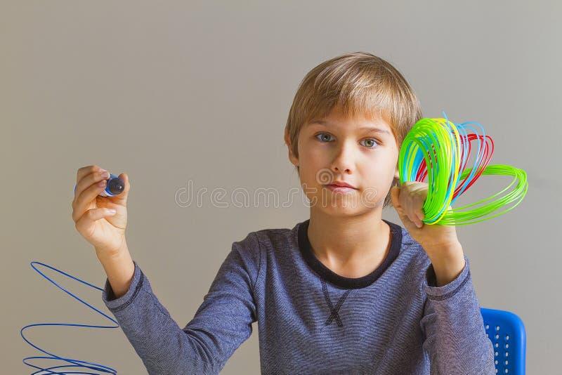 Chłopiec trzyma 3 d pióro i kolorowych druciki obrazy royalty free