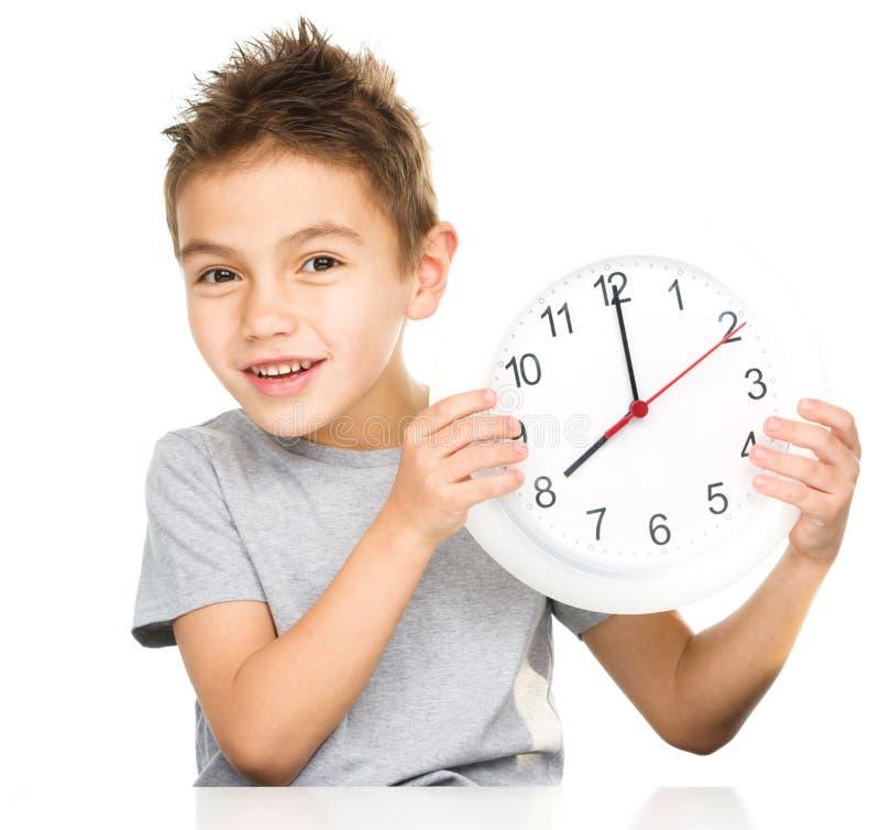 Chłopiec trzyma dużego zegar obraz stock