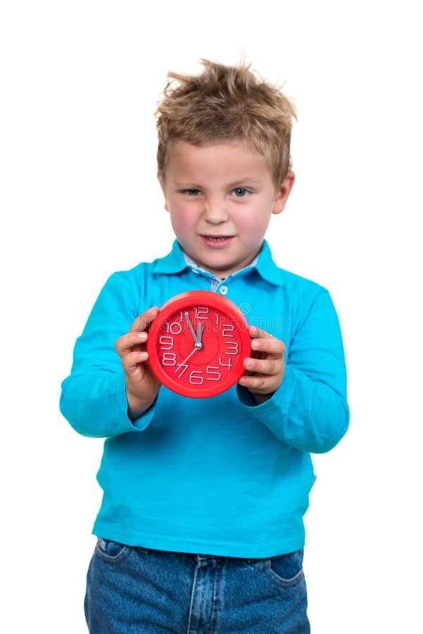 Chłopiec trzyma dużego zegar, odosobniony nadmierny biel fotografia stock
