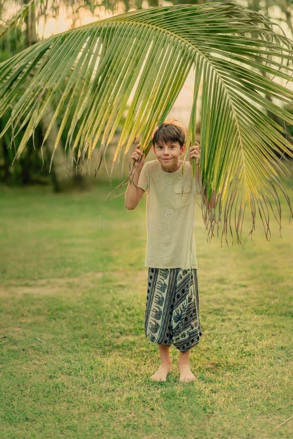 Chłopiec trzyma palmową gałąź na zielonej trawie fotografia royalty free