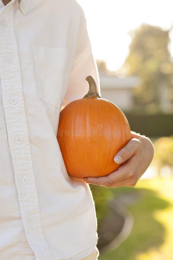 Chłopiec trzyma pomarańczowej cukrowej bani outdoors zdjęcia stock