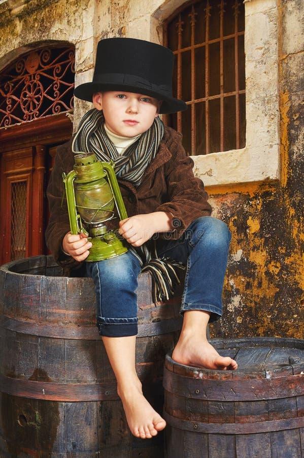 Chłopiec trzyma starą nafty lampę w jego rękach portreta stylizowany retro fotografia royalty free