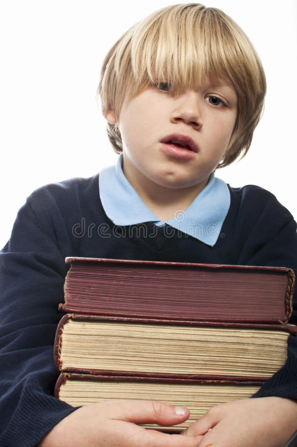 Chłopiec trzyma stertę książki obraz stock