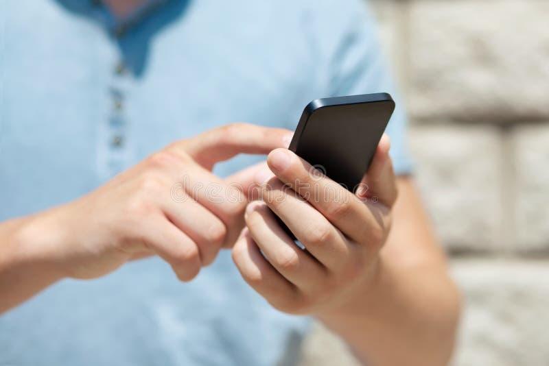 Chłopiec trzyma telefon i dotyka ekran dla palca przeciw ścianie fotografia royalty free