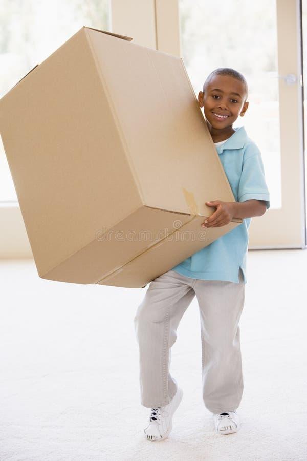 chłopiec trzymający pudełkowy domu nowe uśmiechnięci young fotografia stock