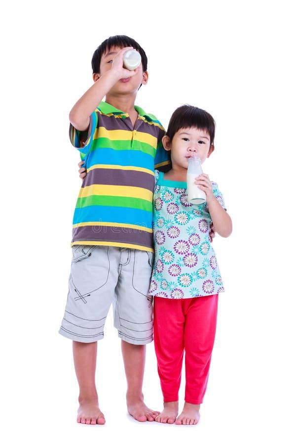 Chłopiec uśmiecha się butelkę mleko i trzyma, na bielu fotografia royalty free
