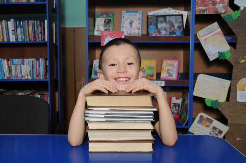 Chłopiec uśmiechnięty obsiadanie w bibliotece, kładzenie głowa na stosie książka zdjęcia royalty free