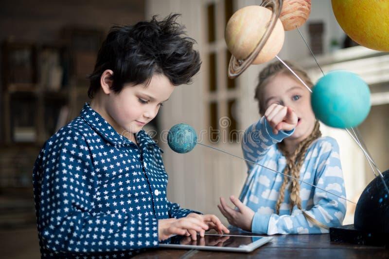 Chłopiec używa cyfrową pastylkę podczas gdy dziewczyna wskazuje na układu słonecznego modelu zdjęcie royalty free