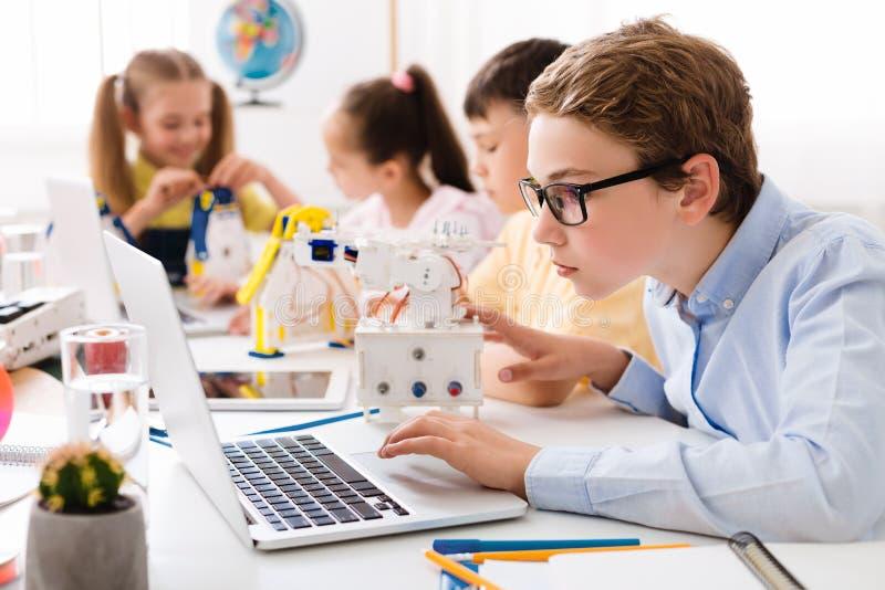 Chłopiec używa laptop, gromadzić robot w klasie obraz stock