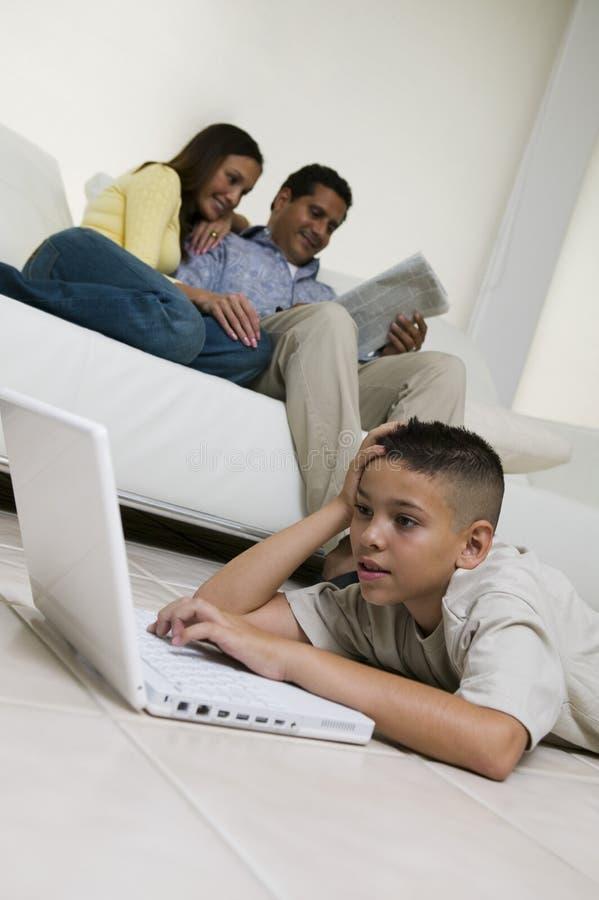 Chłopiec Używa laptop na podłoga w żywej pokój matce, ojcu na kanapa zmielonym widoku i obraz stock