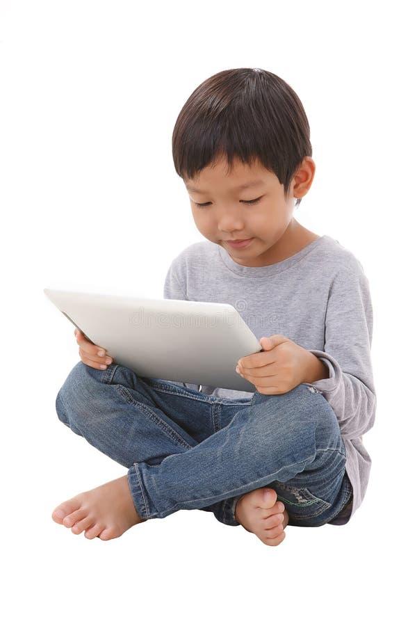 Chłopiec używa pastylkę podczas gdy siedzący fotografia stock
