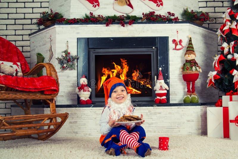 Chłopiec ubierał jak boże narodzenie elfa obsiadanie blisko choinki grabą, łasowań ciastka i pić mleko zdjęcia royalty free