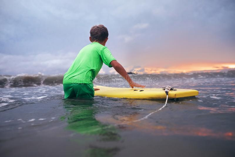Chłopiec uczenie surfować w ocean fala przy zmierzchu czasem zdjęcia stock