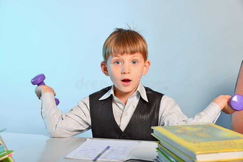 Chłopiec uczy kogoś dumbbell rozgrzewkę i robi jest zmęczona dom podczas gdy siedzący przy stażowym stołem przy szkołą zdjęcie royalty free