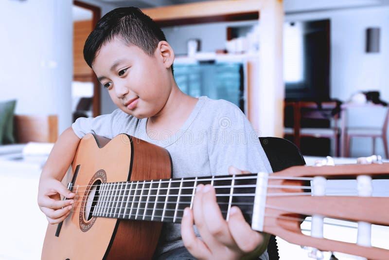 Chłopiec uczy się bawić się gitarę fotografia royalty free