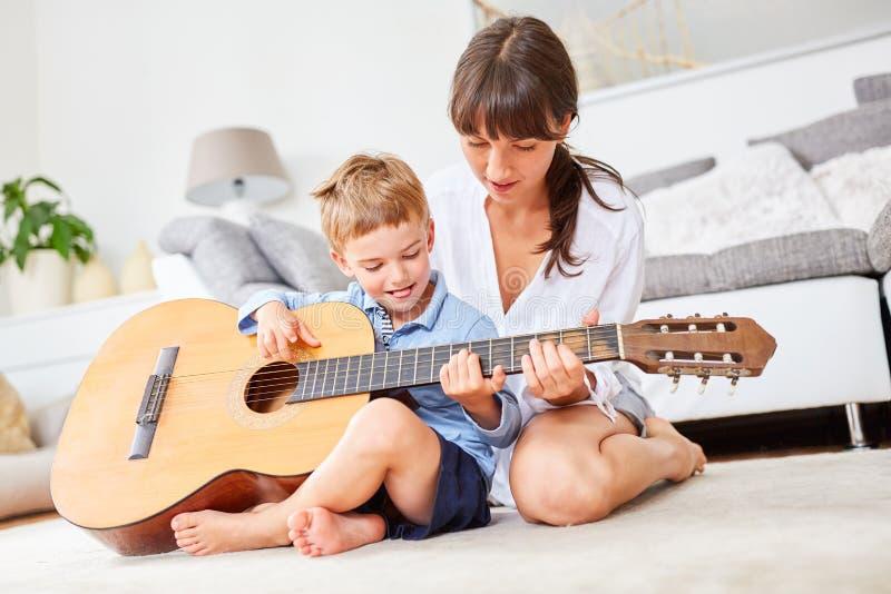 Chłopiec uczy się bawić się gitarę w domu fotografia royalty free