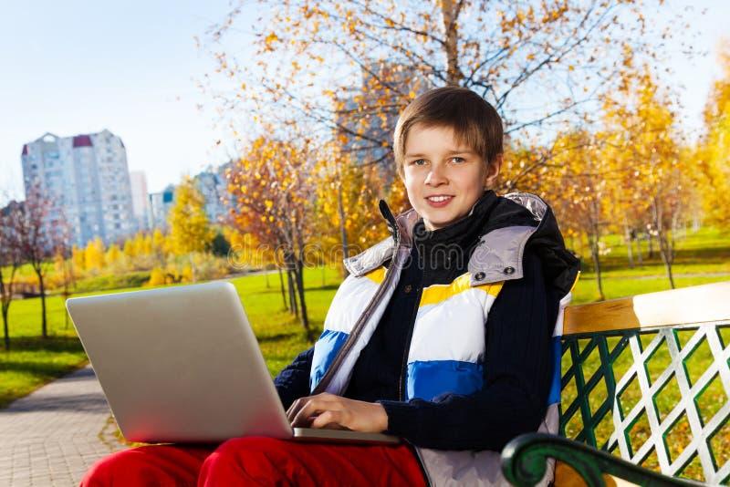 Chłopiec uczy się z laptopem outside fotografia stock