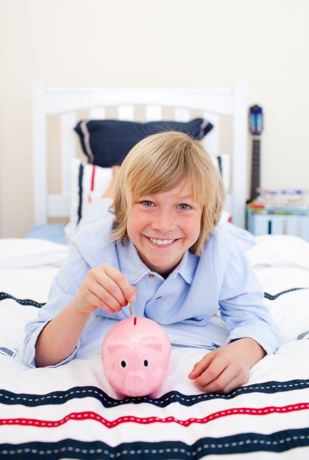 Download Chłopiec Ukuwać Nazwę Piggybank Kładzenia Ja Target2276_0_ Obraz Stock - Obraz złożonej z łakomstwo, przychody: 13341733