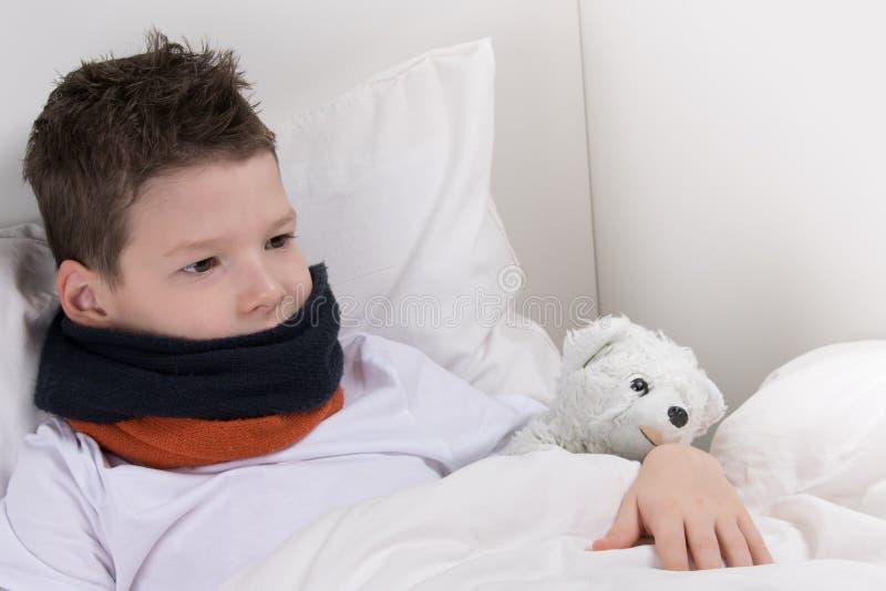 Chłopiec w łóżku, z bolesnym gardłem, odzyskuje fotografia stock