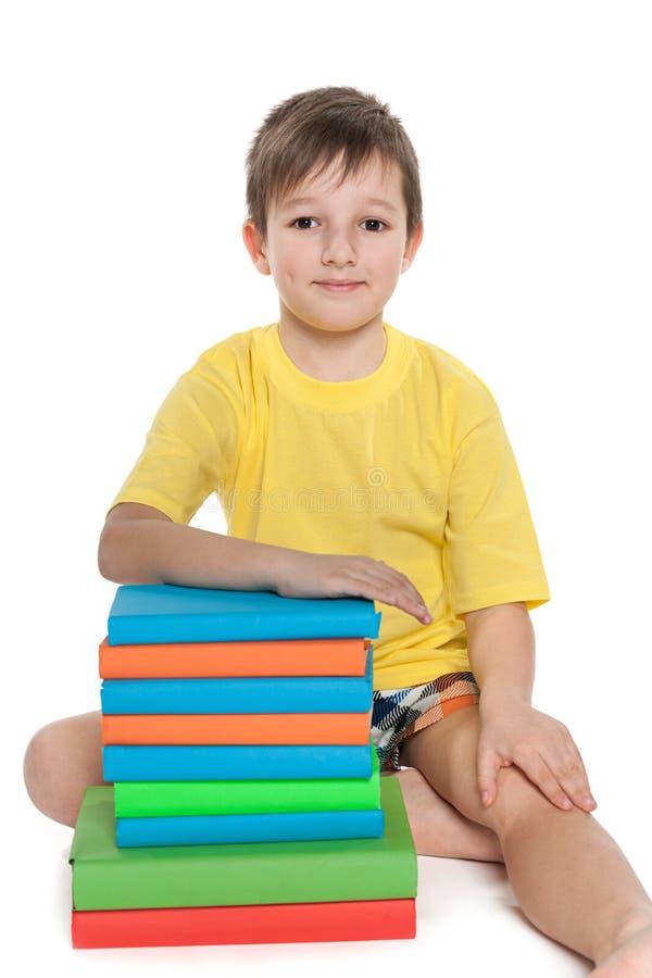Chłopiec w żółte koszulowe pobliskie książki zdjęcia stock