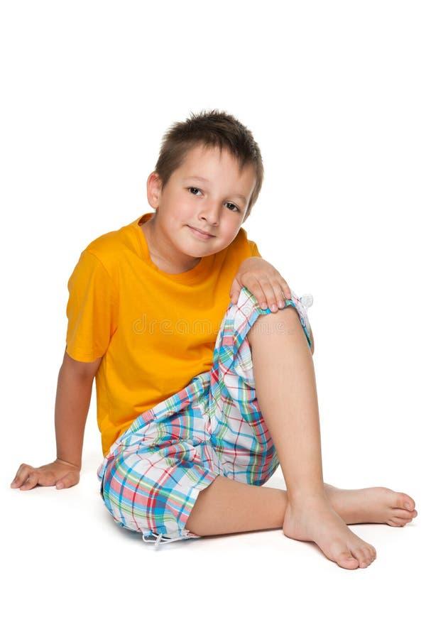 Chłopiec w żółtej koszula siedzi obraz stock