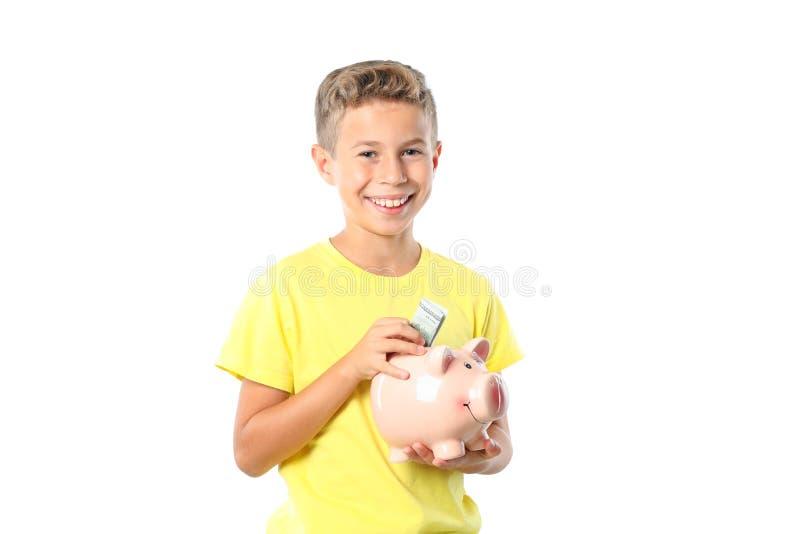 Chłopiec w żółtej koszulce z prosiątko bankiem odizolowywającym zdjęcia stock
