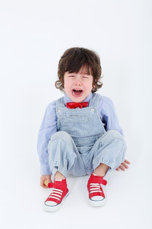 Chłopiec w błękitnym kombinezonie siedzi na podłoga i płacze obrazy stock
