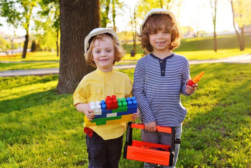 Chłopiec w białych budowa hełmach bawić się w pracownikach z zabawkarskimi narzędziami obraz stock