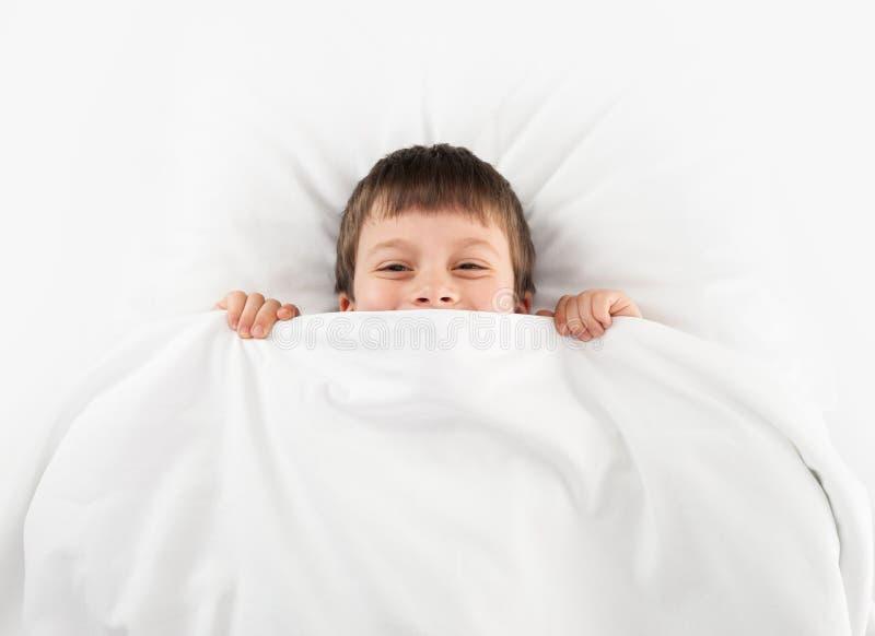 Chłopiec w białym łóżku zdjęcia royalty free