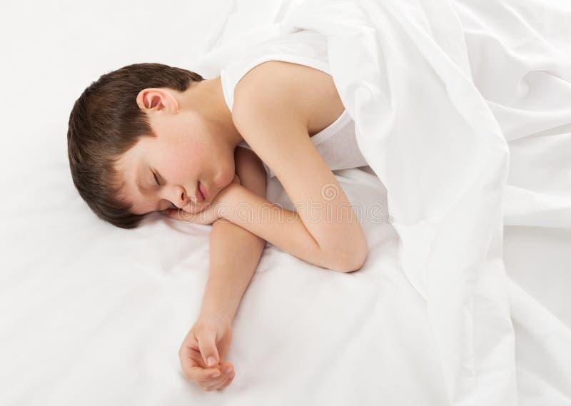 Chłopiec w białym łóżku zdjęcia stock