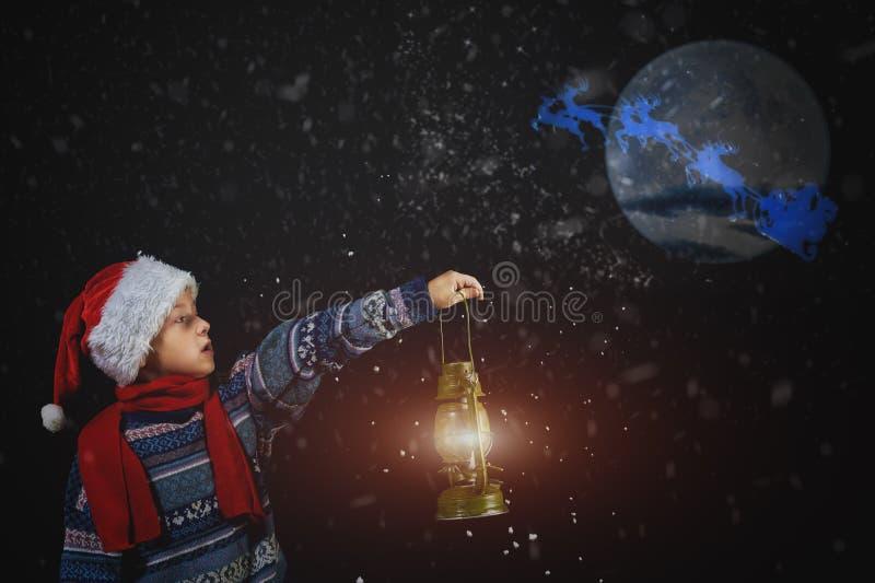 Chłopiec w Bożenarodzeniowym kapeluszu z lampionem w ręce, punkty sposobu Święty Mikołaj latanie na jego saniu z księżyc obraz stock