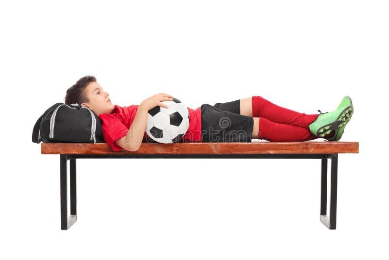 Chłopiec w czerwonym futbolowym dżersejowym lying on the beach na ławce obrazy royalty free