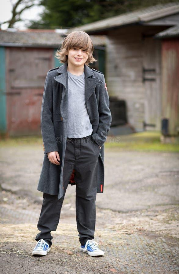 Chłopiec w Długiej żakiet pozyci w Rolnym jardzie zdjęcia royalty free