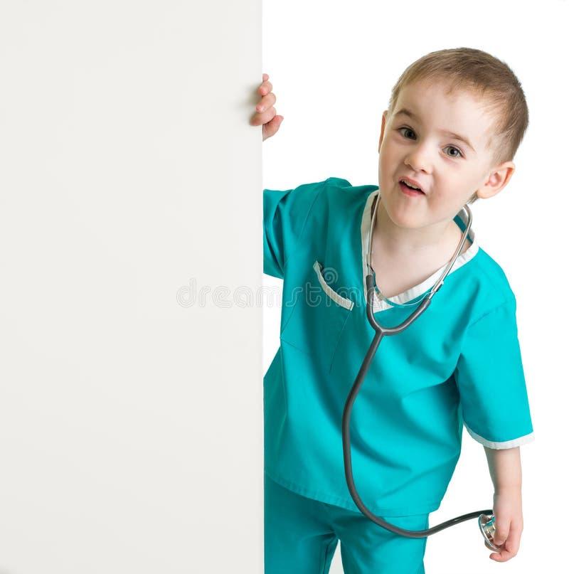 Chłopiec w doktorskim kostiumu za pustym sztandarem odizolowywającym obraz stock