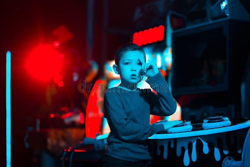 Chłopiec w gemowym pokoju z karabinami maszynowymi Neonowy światło _ fotografia royalty free