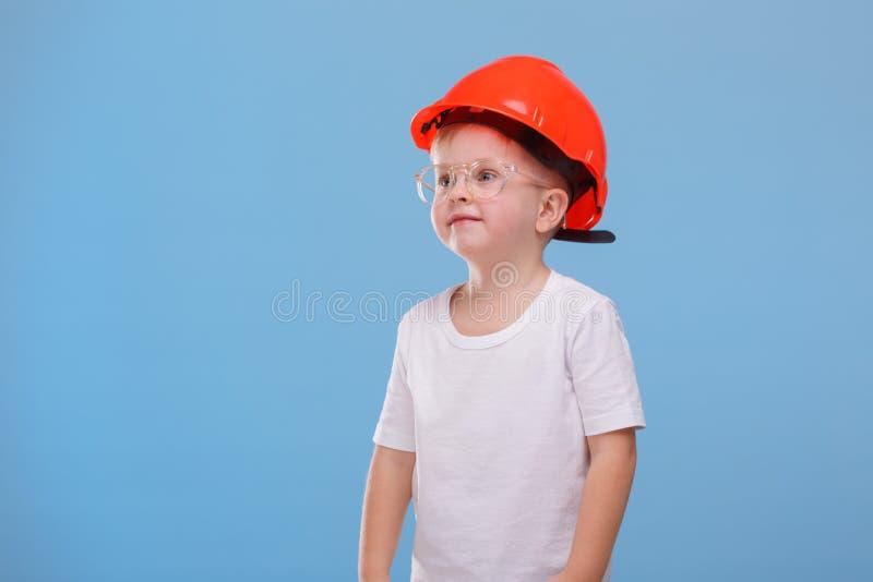 Chłopiec w hełma spojrzeniach w stronie na błękitnym tle zdjęcia royalty free