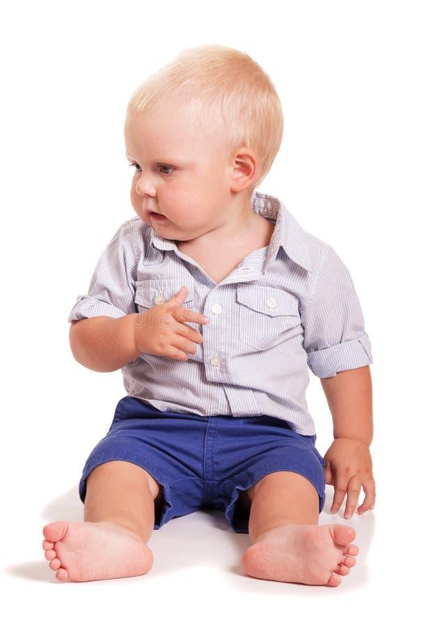 Chłopiec w jaskrawej koszula z lampasami, skrótów siedzieć odizolowywam zdjęcia stock