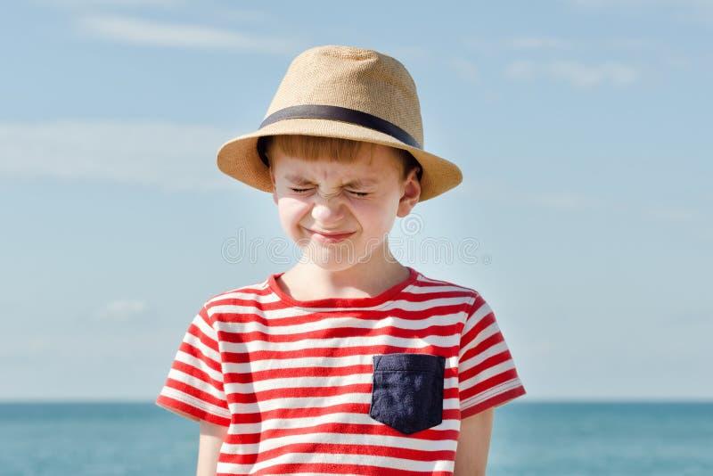 Chłopiec w kapeluszowym zezowaniu od słońca morze na tle zdjęcie royalty free