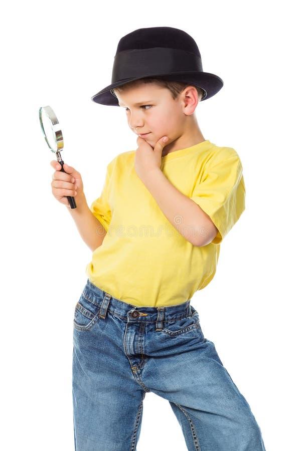 Chłopiec w kapeluszu z powiększać - szkło zdjęcie stock