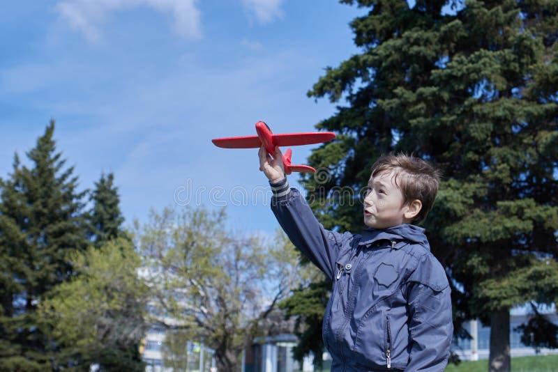 Ch?opiec w kurtce wszczyna piankowego samolot fotografia stock