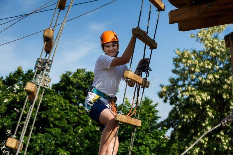 Chłopiec w lasowym przygoda parku Dzieciak w pomarańczowym hełmie i białe t koszulowe wspinaczki na wysokim linowym śladzie Wspin fotografia stock